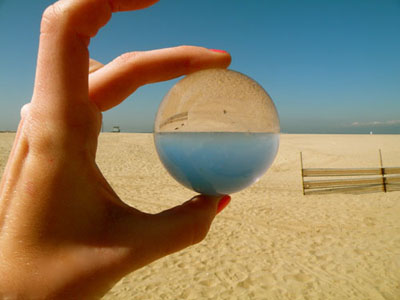 This photo was contrived by placing a transparent sphere against the beach horizon. By matching the refraction from the sphere with the point where the shoreline and skyline meet, this photo demonstrates the physics of refraction. By means of refraction, lenses form an image. The glass sphere in this photo acted as a lens causing the inverted image. This photo was taken at the Venice beach in Los Angeles, California and shows the beauty of combining physics with ones own natural surroundings.